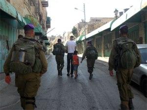 הילד ואביו מובלים למחסום. (צילום: בצלם)